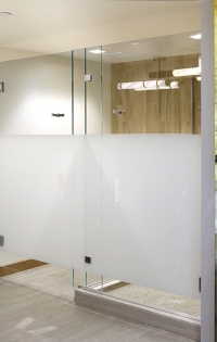 "Features: A partition wall of 1/2"" low-iron, imaged glass hangs from heavy-duty trolley system featuring motion dampeners and soft-close technology. Sliding wall closes to fixed partition, completing the imprinted image. Inside are side-by-side water closets and frameless shower enclosures featuring privacy treatments using the same Imaged glass process."